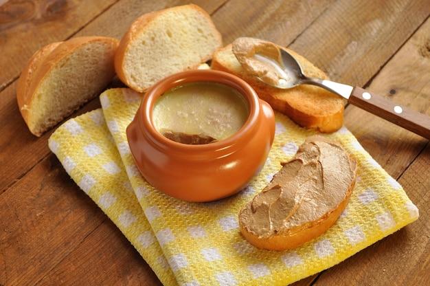 Tosti la pagnotta e un vaso ceramico con patè su fondo di legno Foto Premium