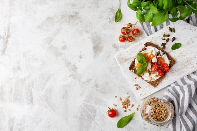 Fetta di pane tostato con pomodorini sul tavolo di marmo copia spazio Foto Premium