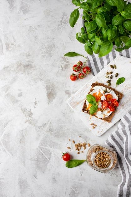 Fetta di pane tostato con pomodorini su fondo di marmo Foto Premium