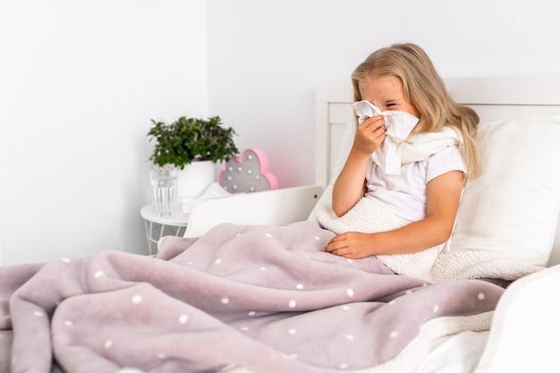 La ragazza del bambino è sdraiata a letto. il bambino ha freddo e malato e ha il naso che cola e il moccio. Foto Premium