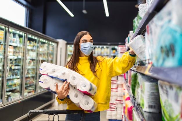 Carenza di carta igienica donna con maschera igienica che acquista forniture di carta igienica a causa di acquisti di panico e accumulo di prodotti durante l'epidemia di virus. Foto Premium
