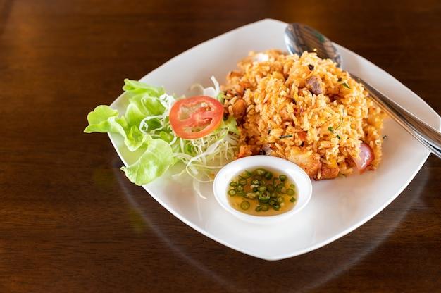 Tom yum riso fritto con carne di maiale croccante sulla tavola di legno Foto Premium
