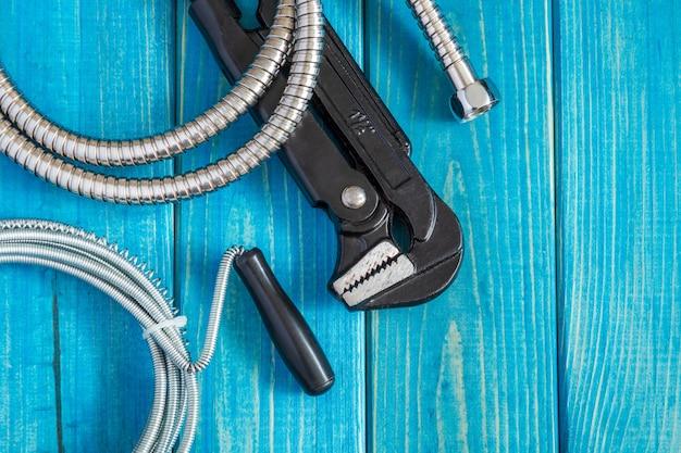 Strumenti e tubo flessibile per idraulico maestro su tavole di legno blu vintage, piatto lay Foto Premium