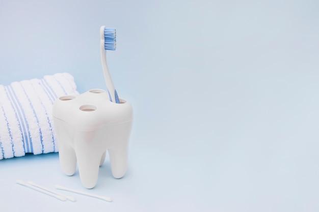 Spazzolino da denti; tampone di cotone e asciugamano su sfondo blu Foto Premium