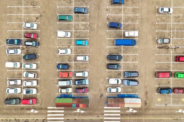 Vista aerea dall'alto in basso di molte auto in un parcheggio di un supermercato o in vendita sul mercato del concessionario auto Foto Premium