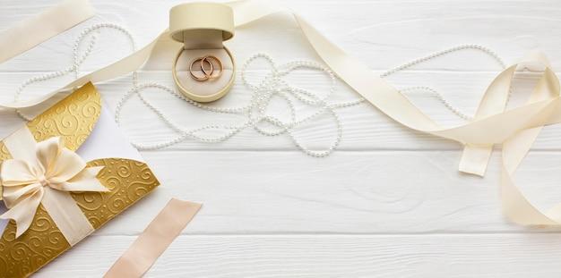 Disposizione vista dall'alto di perle e fedi nuziali Foto Premium