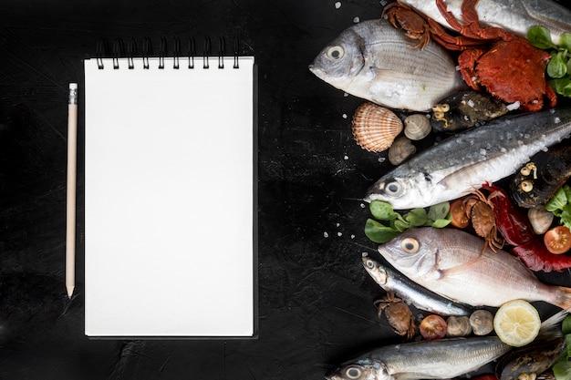 Vista dall'alto dell'assortimento di frutti di mare con blocco note Foto Premium