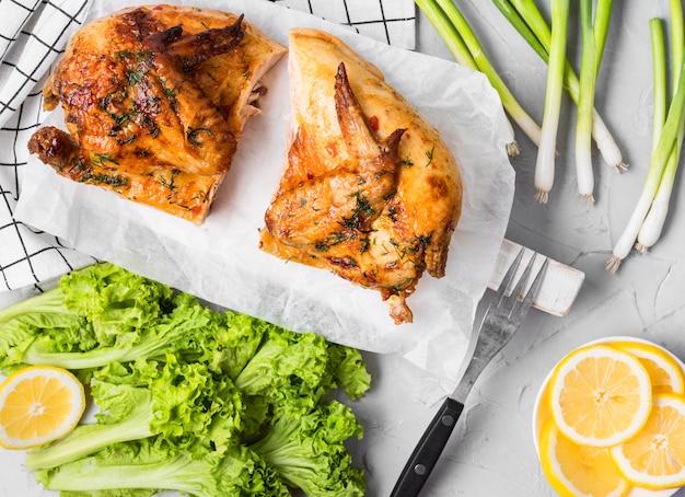 Vista dall'alto di pollo intero al forno a metà con insalata Foto Premium