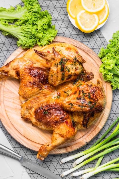 Vista dall'alto pollo intero al forno con fette di limone, cipolla verde e insalata Foto Premium