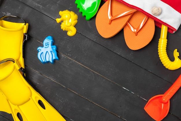 Vista dall'alto di una composizione essenziale di spiaggia di giocattoli di plastica e attrezzatura per lo snorkeling Foto Premium