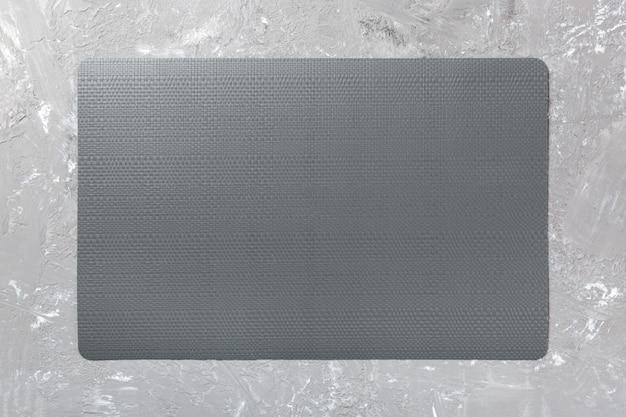 Vista dall'alto della tovaglietta nera per un piatto. sfondo di cemento Foto Premium