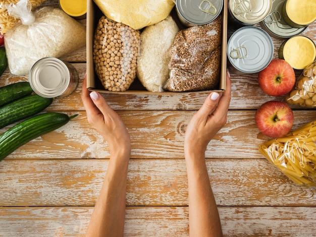 Vista dall'alto della scatola con il cibo per la donazione e le mani Foto Premium