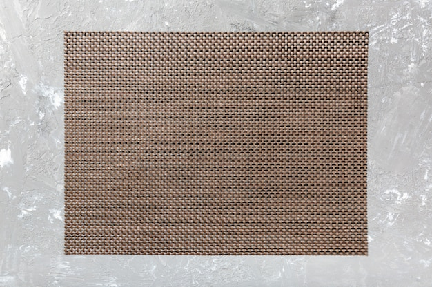 Vista superiore del tovagliolo di tavola marrone sul fondo del cemento. tovaglietta con spazio vuoto Foto Premium
