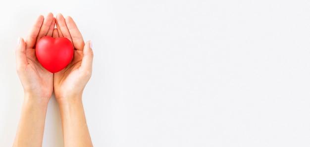 Vista dall'alto delle mani premurose che tengono il cuore con lo spazio della copia Foto Premium