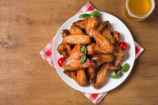 Vista dall'alto ali di pollo sul piatto con semi di sesamo e birra Foto Premium