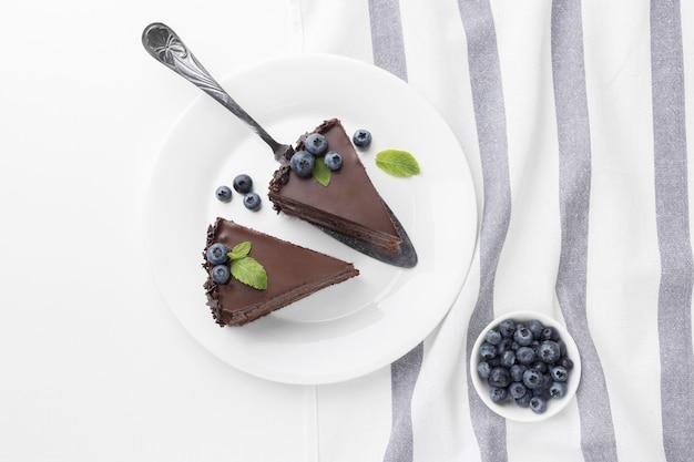 Vista dall'alto di fette di torta al cioccolato su piastre con ciotola di mirtilli Foto Premium