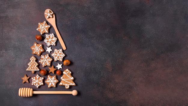 Vista dall'alto della forma dell'albero di natale fatta di biscotti di panpepato e utensili da cucina con spazio di copia Foto Premium