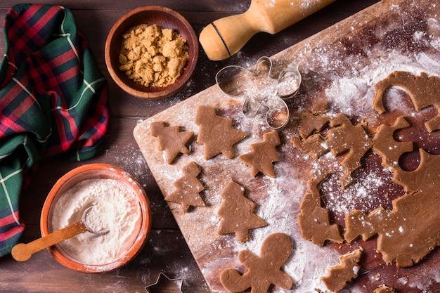 Vista dall'alto della pasta biscotto degli alberi di natale con il mattarello Foto Premium
