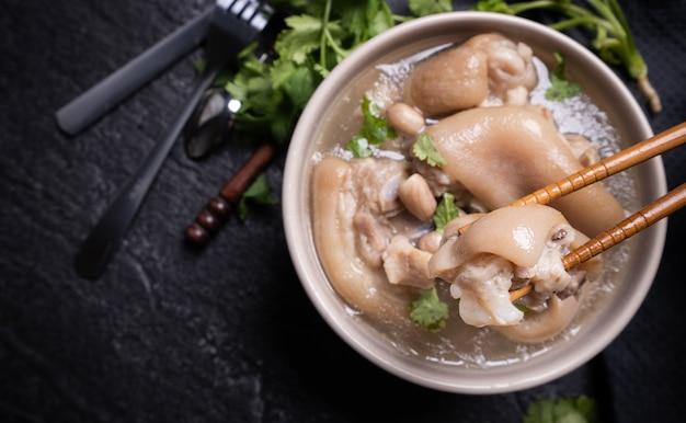 Vista dall'alto, primo piano, copia spazio, cibo di strada distintivo asiatico di taiwan, zuppa di stinco di maiale di arachidi in una ciotola di color bianco crema avorio beige isolata sul tavolo di ardesia scisto scuro Foto Premium