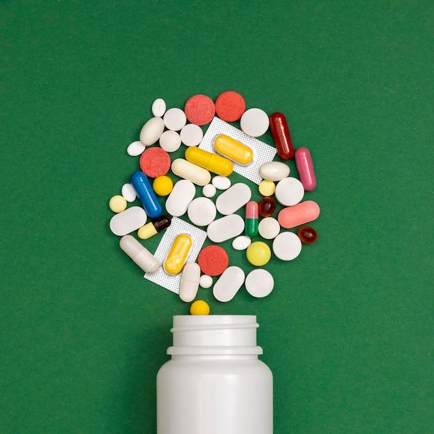 Vista superiore del contenitore che rovescia varietà di pillole Foto Premium