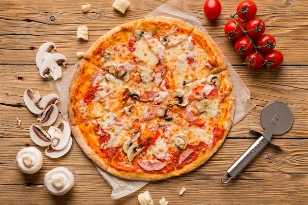 Vista dall'alto di una deliziosa pizza sul tavolo di legno Foto Premium