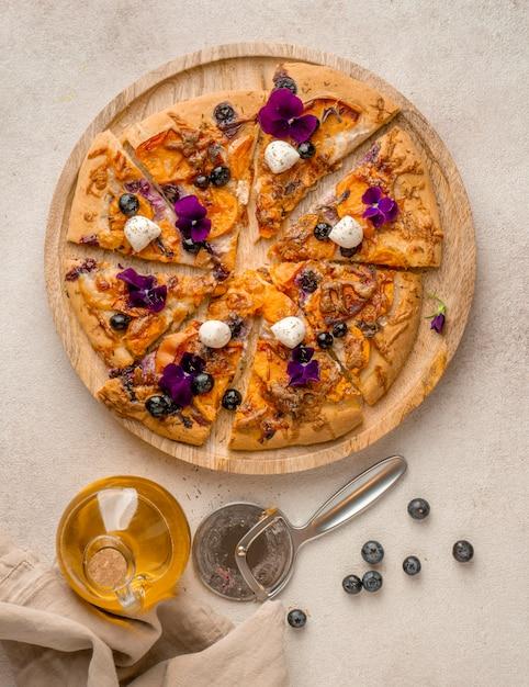 Vista dall'alto di una deliziosa fetta di pizza con mirtilli e petali di fiori Foto Premium