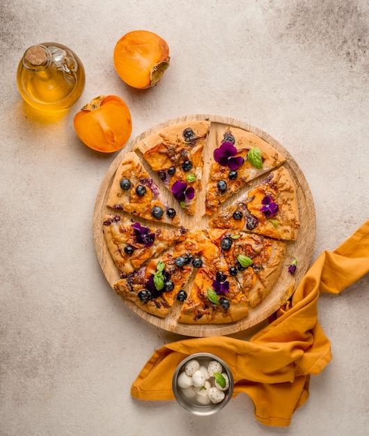 Vista dall'alto di una deliziosa fetta di pizza con petali di fiori e cachi Foto Premium