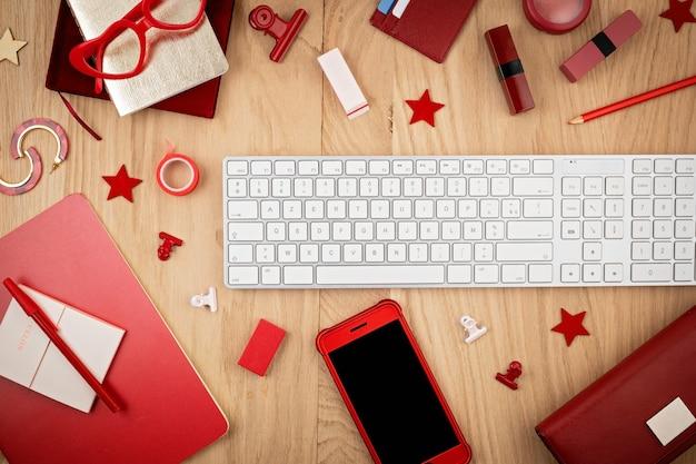 Vista dall'alto del desktop con stazionario rosso per ufficio, smart phone e tastiera. lat lay. spazio ufficio, concetto di home office Foto Premium