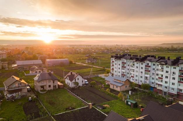 Vista dall'alto dello sviluppo del paesaggio della città. tetti della casa della periferia e della costruzione di appartamento sul cielo rosa al fondo di alba. Foto Premium
