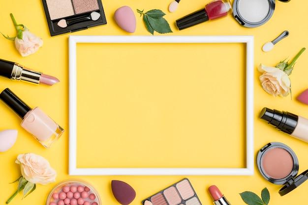 Vista dall'alto disposizione di diversi prodotti di bellezza con cornice vuota Foto Premium