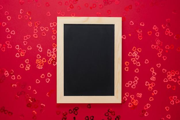 Vista superiore della lavagna vuota su fondo rosso con coriandolo brillante. Foto Premium