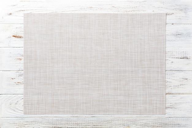 Vista superiore della tovaglia bianca vuota sulla tavola di legno Foto Premium
