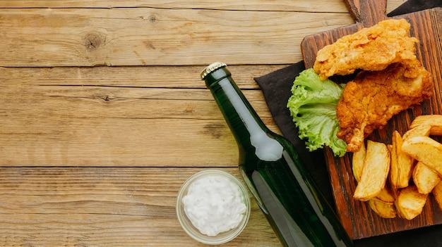 Vista dall'alto di fish and chips con salsa e bottiglia di birra Foto Premium