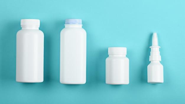 Vista dall'alto quattro bottiglie di contenitori medici bianchi su sfondo blu per mock up e branding Foto Premium