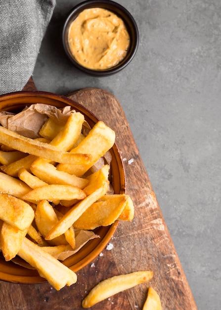Vista dall'alto di patatine fritte in una ciotola con sale e senape Foto Premium
