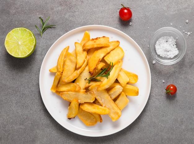 Vista dall'alto di patatine fritte sulla piastra con sale e pomodori Foto Premium