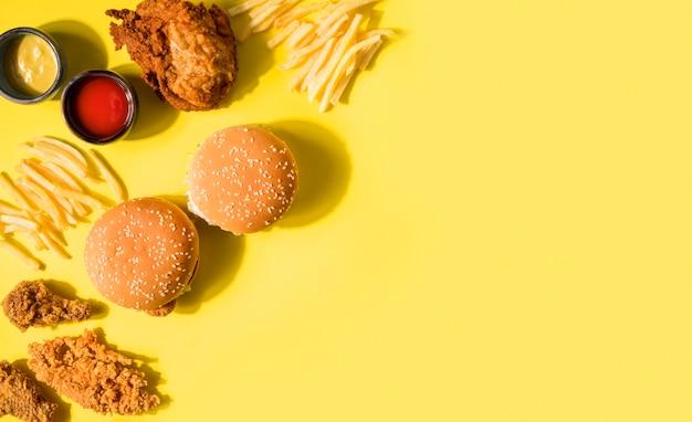 Vista dall'alto pollo fritto, hamburger e patatine fritte con copia-spazio Foto Premium