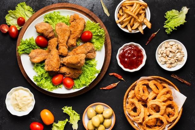 Vista dall'alto di pollo fritto e anelli di cipolla Foto Premium