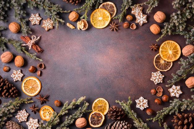 Vista dall'alto di biscotti di panpepato con pigne e cornice di agrumi secchi Foto Premium