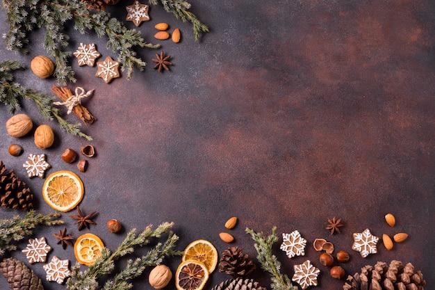 Vista dall'alto di biscotti di panpepato con pigne e agrumi secchi Foto Premium