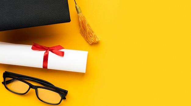 Vista dall'alto di occhiali con cappello accademico e diploma Foto Premium