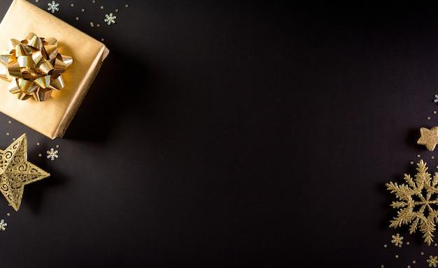 Vista dall'alto di scatole di natale dorate, stella e fiocco di neve su sfondo nero Foto Premium