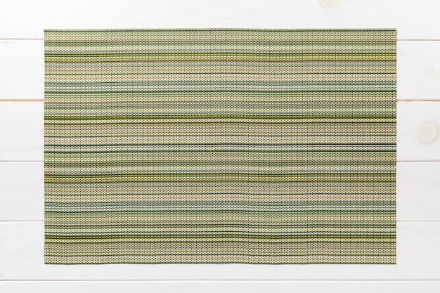 Vista superiore del tovagliolo di tavola verde sulla tavola di legno. tovaglietta Foto Premium