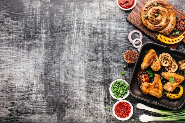 Vista dall'alto di carne alla griglia e verdure sul contesto strutturato in legno Foto Premium