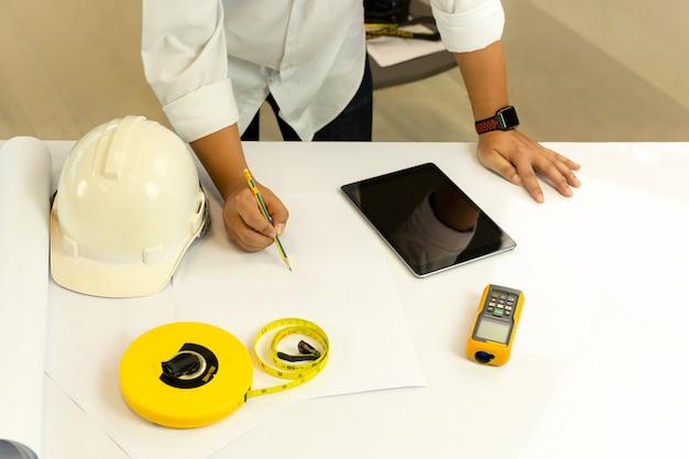 Mano di vista superiore dell'architetto che lavora al modello con il computer della compressa sulla tavola. Foto Premium