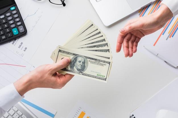 Vista superiore dei soldi della tenuta della mano sopra lo scrittorio Foto Premium
