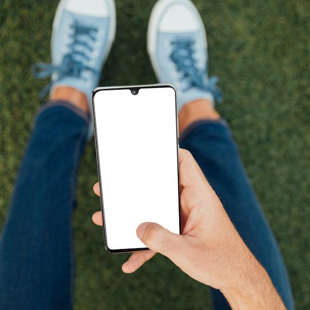 Smartphone della tenuta della mano di vista superiore con il modello Foto Premium