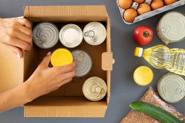 Vista dall'alto della mano che prepara donazioni di cibo nella casella Foto Premium