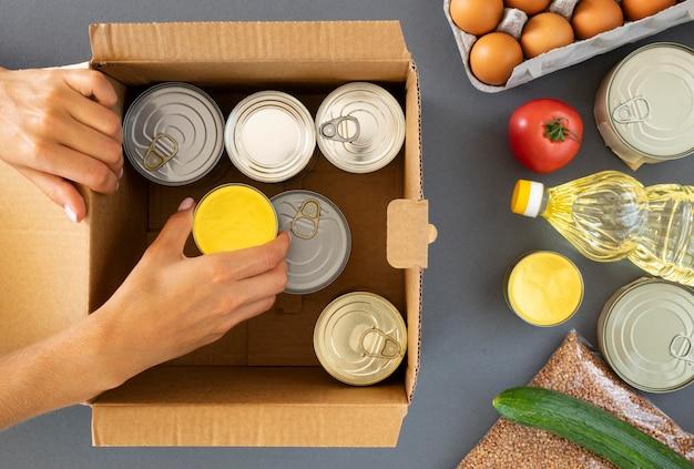 Vista dall'alto della mano che prepara donazioni di cibo Foto Premium