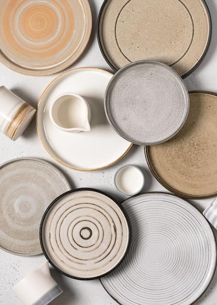 Vista dall'alto di ceramiche fatte a mano, piatti vuoti in ceramica artigianale e tazze su sfondo chiaro. Foto Premium